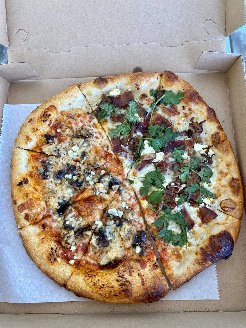 This half-and-half pie from Dolos Pizza is half a Matey pizza (marinara, mozzarella, jerk chicken, blue cheese and honey) and half a Mr. Rager (garlic crema, bacon, mushrooms, goat cheese, cilantro). Wendell Brock for The Atlanta Journal-Constitution