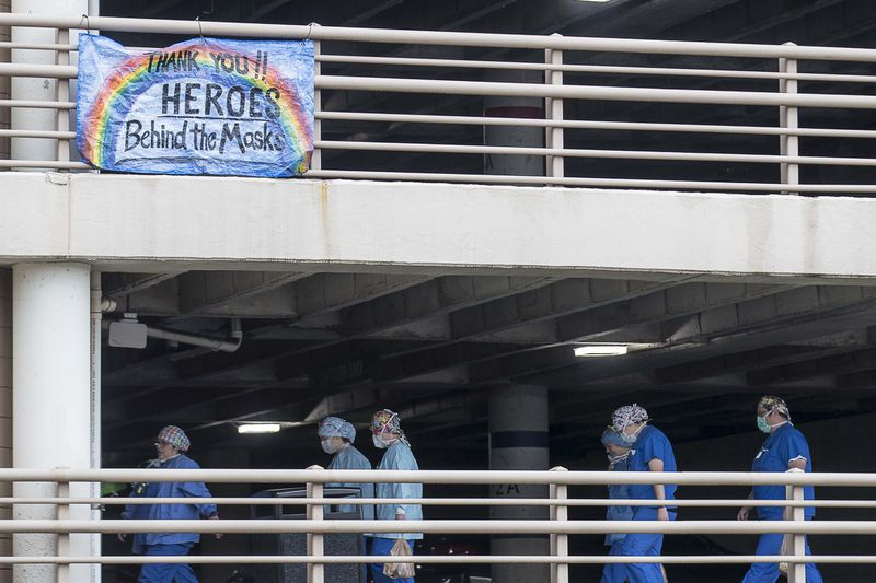 In this photo from April, early in the pandemic, health workers walk toward the entrance of Floyd Medical Center in Rome, Georgia.  The hospital in northwest Georgia saw one of the state's first COVID-19 surges. (PHOTO by ALYSSA POINTER / Alyssa.Pointer@AJC.com)