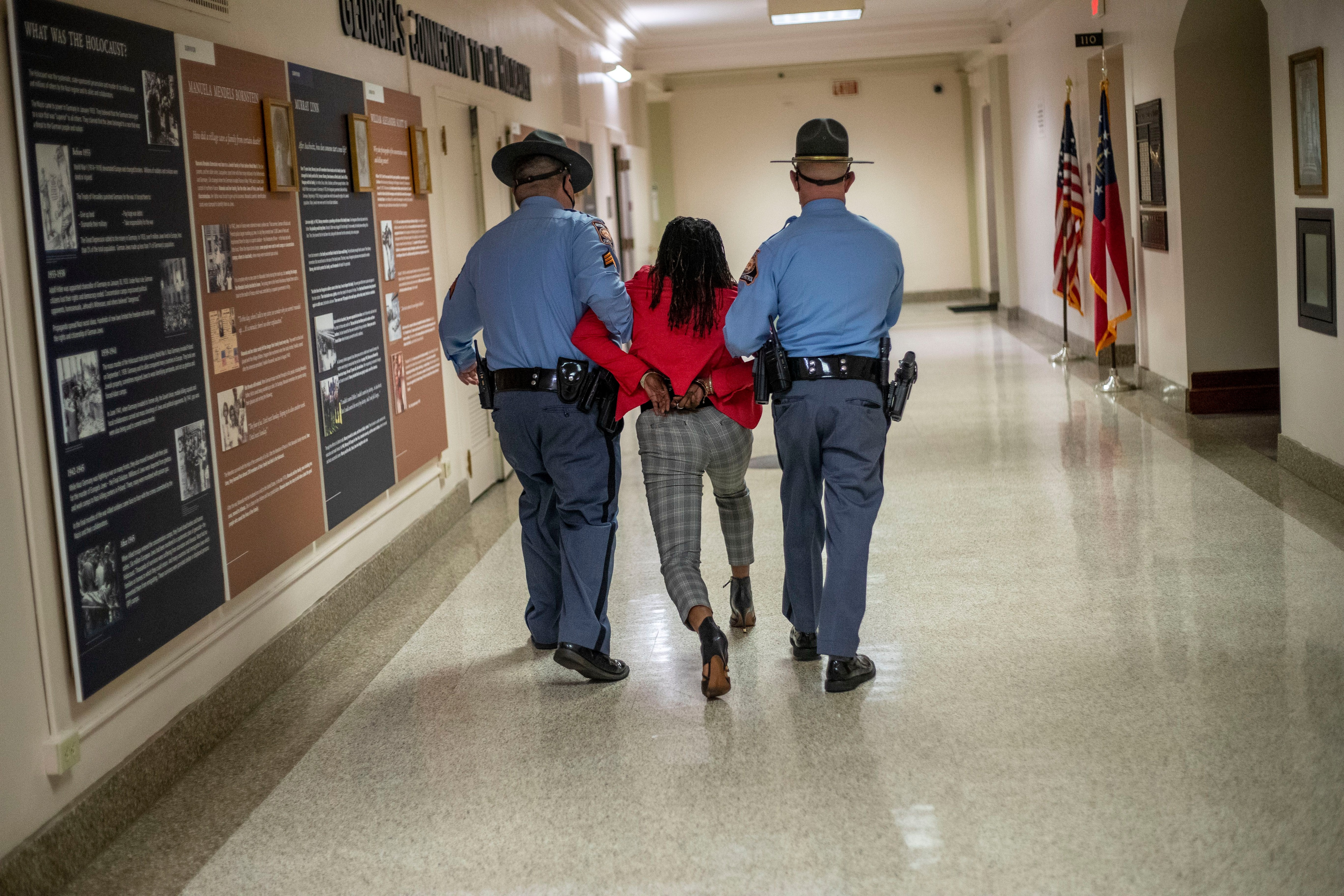 03/25/2021 —Atlanta, Georgia — Rep. Park Cannon (D-Atlanta) is escorted out of the Georgia Capitol Building by Georgia State Troopers after being asked to stop knocking on a door that lead to Gov. Brian Kemp's office while Gov. Kemp was signing SB 202 behind closed doors on day 38 of the legislative session at the Georgia State Capitol Building in Atlanta, Thursday, March 25, 2021. (Alyssa Pointer / Alyssa.Pointer@ajc.com)