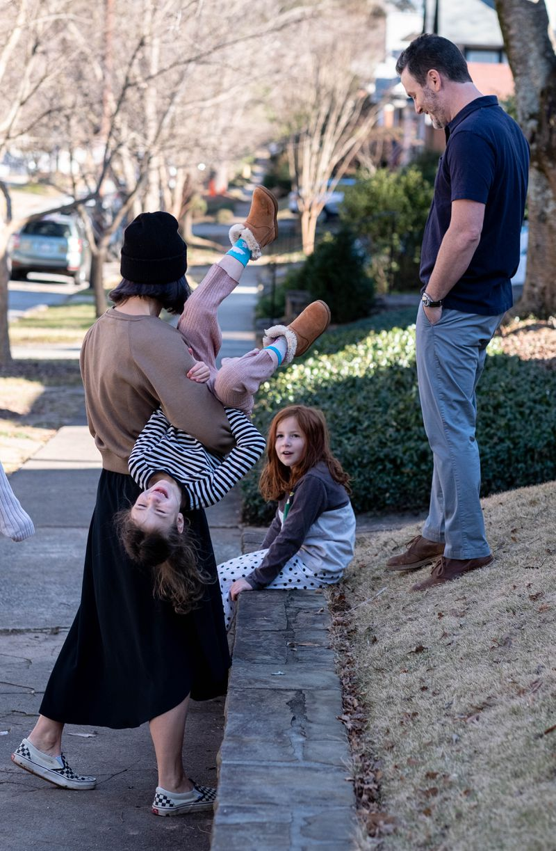 210115-Atlanta-Jennifer Holdbach flips her daughter Laly, 6, over while her and her husband Evan Cohn talk to one of their other daughters Etta, 8, Friday, Jan. 15, 2021 at their home in Virginia-Highland.  Ben Gray for the Atlanta Journal-Constitution