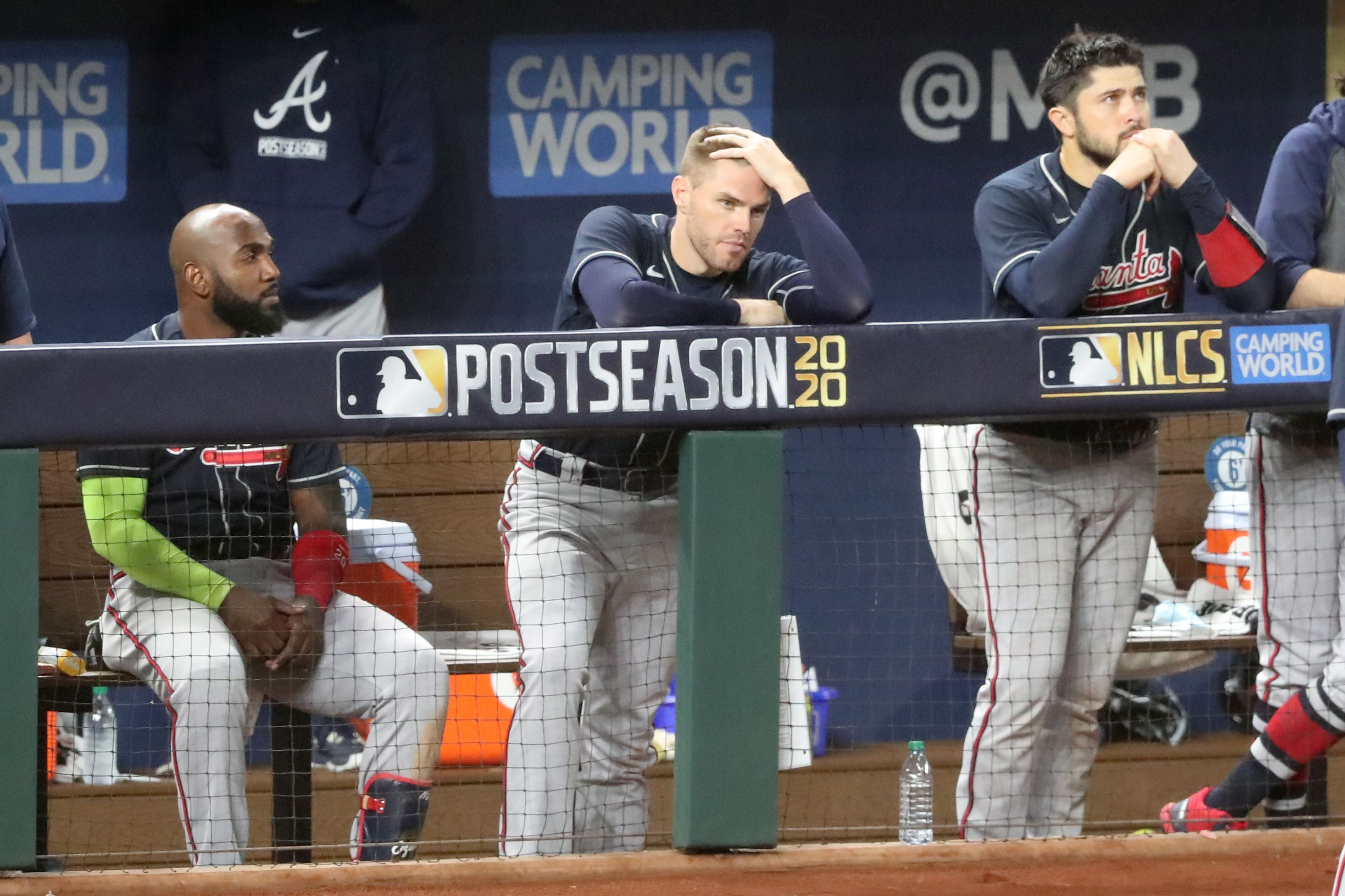 Braves players (from left) Marcell Ozuna, Freddie Freeman and Travis d'Arnaud watch the final outs of Game 7 of the National League Championship Series against the Los Angeles Dodgers Sunday, Oct. 18, 2020, at Globe Life Field in Arlington, Texas. The Dodgers won the game 4-3 and the series 4-3.  (Curtis Compton / Curtis.Compton@ajc.com)