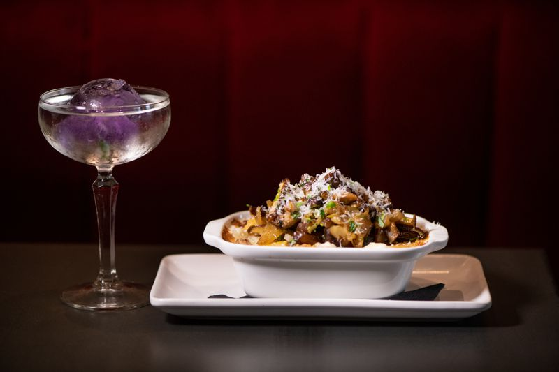 The Continent's Cassava Au Gratin side dish is shown with the Stush Martini, made with rum, dry vermouth, white cranberry juice, and fresh lime juice and served with an orchid flower-infused ice ball. (Mia Yakel for The Atlanta Journal-Constitution)