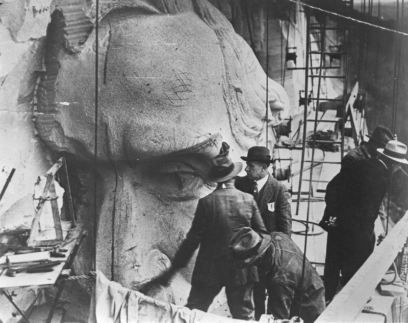 Sculptor Augustus Lukeman (hand on sculpture) inspects the head of Robert E. Lee in this 1928 photograph. Lukeman, who began work on the carving in 1926, was the second sculptor to work on the project. His design formed the basis of the sculpture completed this spring. Gutzon Borglum began work on the mountain in 1923 but left in 1925. His beginning efforts were removed from the mountain. (FILE PHOTO)