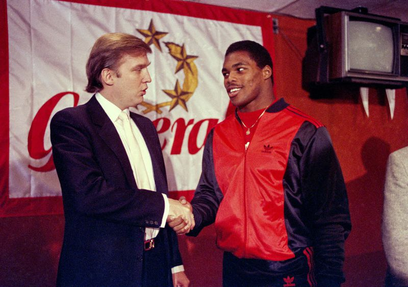 Donald Trump shakes hands with Herschel Walker in New York in March 1984 after agreement on a four-year contract with USFL football team, the New Jersey Generals. (Dave Pickoff/AP)