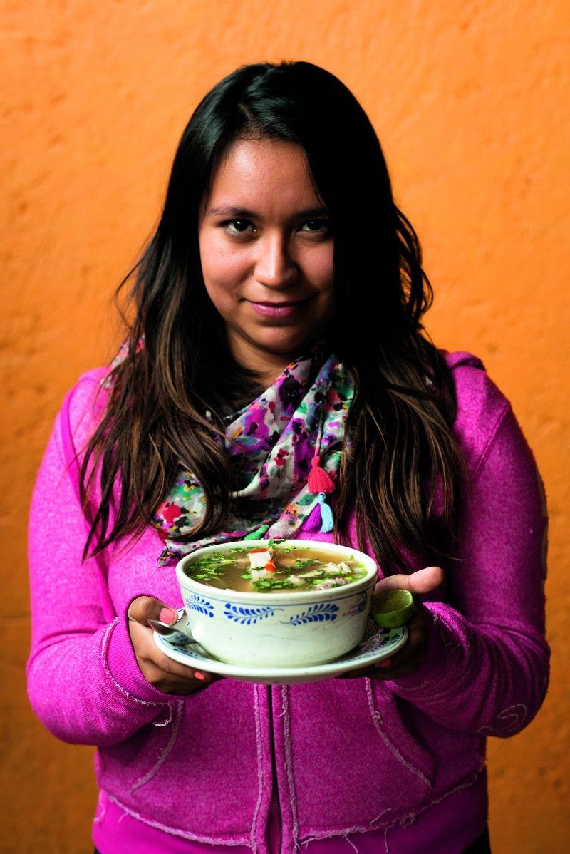 A young woman holds caldo de pollo, Mexico City's answer to chicken in a pot. Courtesy of Ten Speed Press/James Roper © 2020