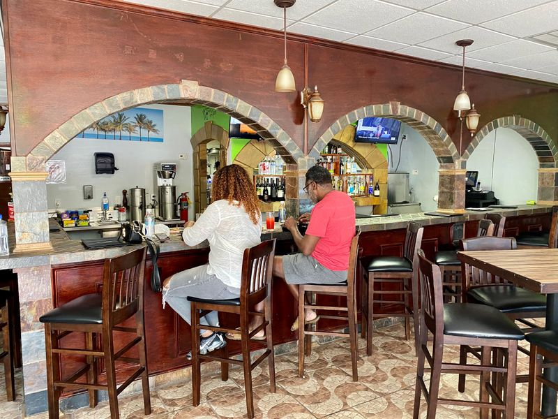 Customers enjoy a meal at the bar at Spicy Hill, a new Jamaican restaurant in Jonesboro. Wendell Brock for The Atlanta Journal-Constitution