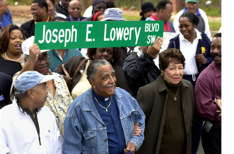 Rev. Joseph Lowery walks arm-in-arm with his wife Evelyn down Ashby Street between Ralph David Abernathy Boulevard and Martin Luther King, Jr. Drive in Southwest Atlanta in 2001. Ashby Street was being changed to Joseph E. Lowery Boulevard. (CHARLOTTE B. TEAGLE/AJC staff)