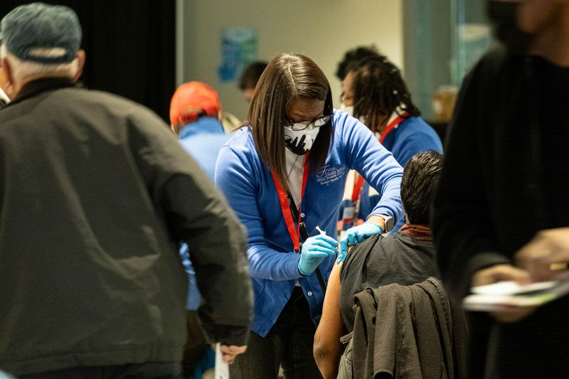 Registered nurse Aleve Reed administers a COVID-19 vaccine during an event in January at Mercedes-Benz Stadium for Fulton County Schools employees and their spouses who are 65 and older. (Ben Gray for The Atlanta Journal-Constitution)