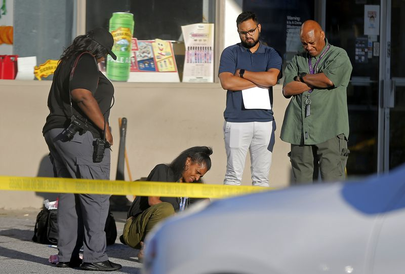 A medical examiner looks over a body at the scene of a shooting in the parking lot of a Chevron station at the corner of Monroe Drive and Piedmont Road in Atlanta on June 21, 2021. A rideshare driver opened fired at the gas station, killing one passenger and injuring another.(Christine Tannous / christine.tannous@ajc.com)