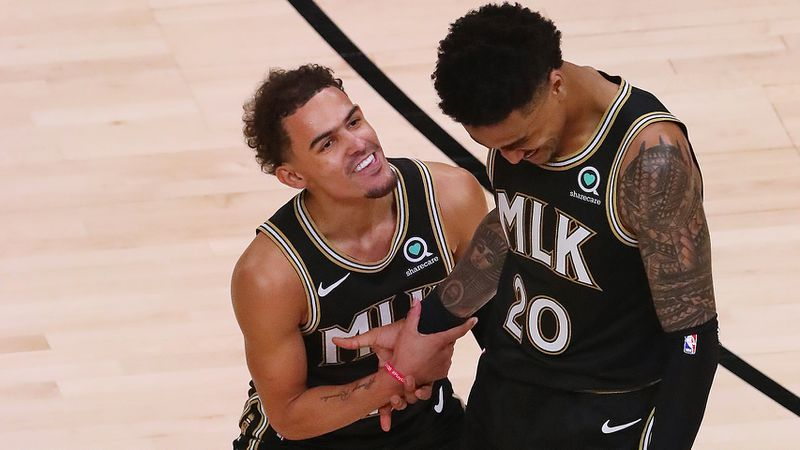 Hawks guard Trae Young celebrates with forward John Collins after he hit a three-pointer adding to Atlanta's second-half lead against the New York Knicks during Game 4 of their first-round NBA playoff matchup Sunday, May 30, 2021, at State Farm Arena in Atlanta. The Hawks beat the Knicks 113-96. (Curtis Compton / Curtis.Compton@ajc.com)