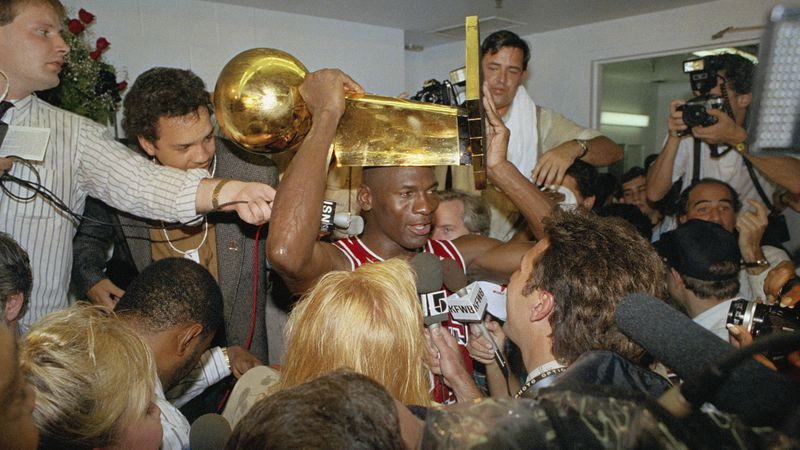 Chicago Bulls Michael Jordan holds the NBA Championship trophy aloft while talking with the media in the locker room after clinching the title with an 108-101 win against the Los Angeles Lakers Wednesday, June 13, 1991, at Inglewood, Calif. (Reed Saxon/AP)