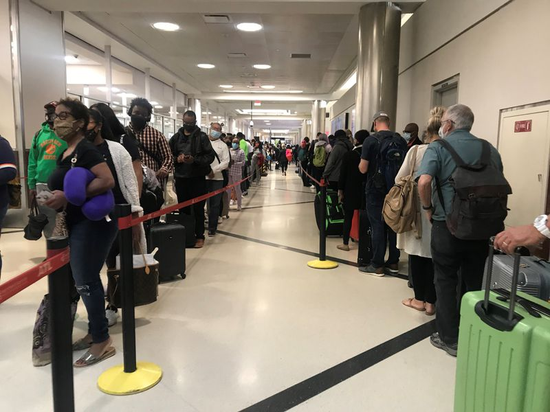 Travelers lined up on one side of an airport hallway for the North security checkpoint, while more lined up on the other side of the hallway for Southwest check-in and baggage check.