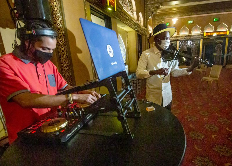 Ashanti Floyd, right, plays music while people wait after getting their COVID vaccination in the lobby of the Fox Theatre earlier this week. (Steve Schaefer for The Atlanta Journal-Constitution)