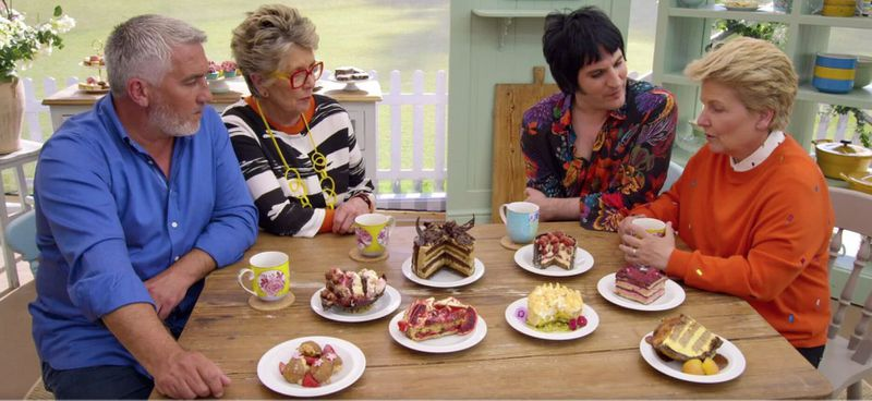 """""""The Great British Baking Show"""" has had a changing cast, in addition to judge Paul Hollywood (left). Here, he's seen with judge Prue Leith and hosts Noel Fielding and Sandi Toksvig. (Courtesy of Netflix)"""