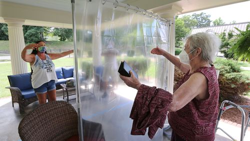 Elsie Grant, 86, sets her walker aside reaching for an air hug from her daughter Wanda Schroeder, socially distanced behind a protective plastic curtain when families could visit loved ones in the outdoor pavilion at Westbury Medical Care & Rehab earlier this month. CURTIS COMPTON / CCOMPTON@AJC.COM