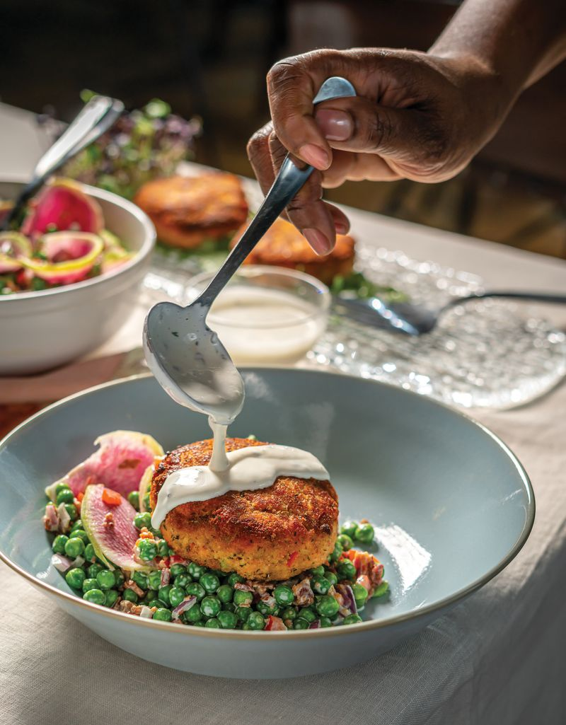 """Buttermilk Dressing is drizzled onto Fresh Salmon Croquettes With Spring Pea, Bacon, and Radish Salad in this image from """"The Twisted Soul Cookbook: Modern Soul Food With Global Flavors"""" (Rizzoli New York, 2021) by Deborah VanTrece. Courtesy of Noah Fecks"""