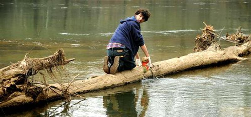 Julian Gindi, perched on a fallen tree, empties out a plastic bottle before bagging it up with other trash he and his buddies collected along the banks of the Chattahoochee River.