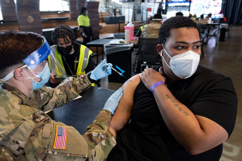 Sgt. Ashley Nazzario administers a COVID-19 vaccine to Ezekiel Dorsey at the mass vaccination site at Mercedes-Benz Stadium on Thursday morning, April 22, 2021. (Ben Gray for The Atlanta Journal-Constitution)