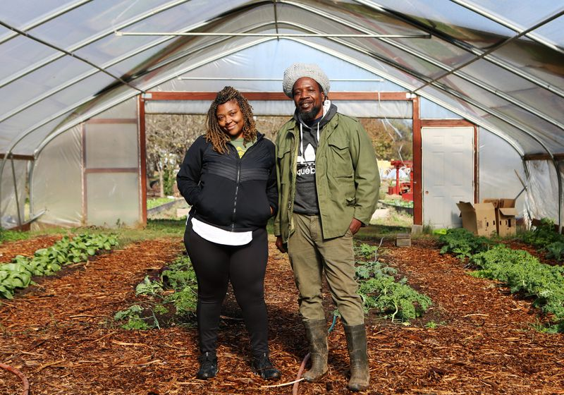 Otis Garrison (right), farm manager at Truly Living Well Farm, and Ivory Flemister (left), media manager at Truly Living Well Farm, pose for a photo in the greenhouse at Truly Living Well Farm in Atlanta on Wednesday, Dec. 2, 2020. Truly Living Well is a non-profit urban farm, and was recently granted the deed to the land. CHRISTINA MATACOTTA FOR THE ATLANTA JOURNAL-CONSTITUTION