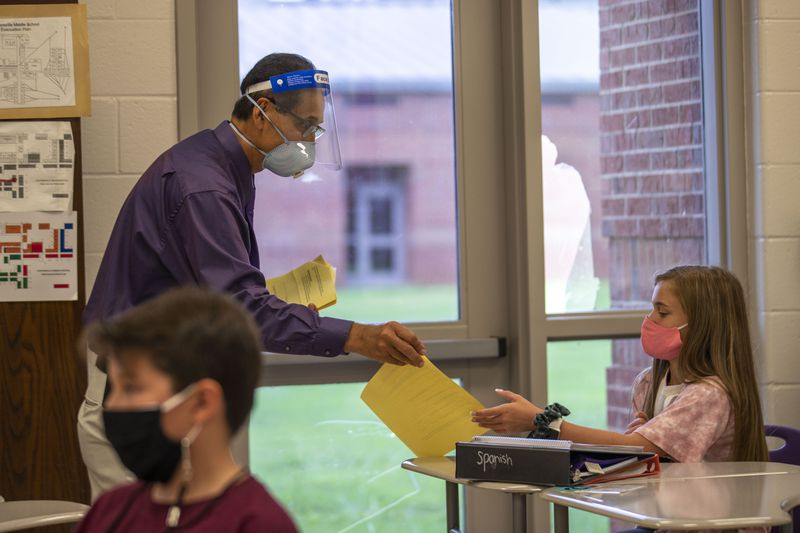 Cartersville Middle School Spanish teacher Omar Nu–ez wears a face mask and a face shield while interacting with students in his classroom at Cartersville Middle School in Cartersville in this Thursday, August 20, 2020 file photo. (ALYSSA POINTER / ALYSSA.POINTER@AJC.COM)