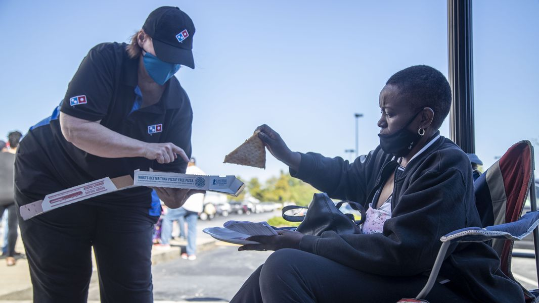 Elaine Scarlett of Lawrenceville takes a free slice of pizza from a Domino's Pizza employee as she waits in line to cast her ballot on the second day of early voting at the Gwinnett County Voter Registration and Elections Building.  (Alyssa Pointer / Alyssa.Pointer@ajc.com)