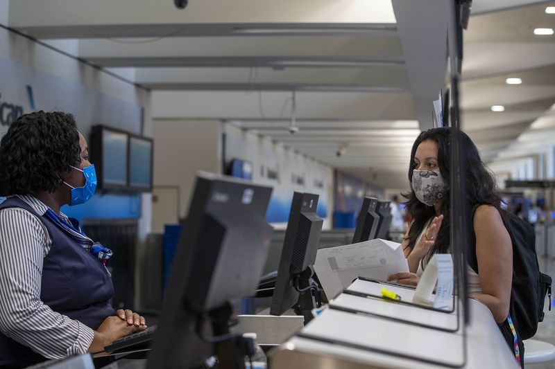 Casa Alterna volunteer Yehimi Cambrón speaks with an American Airlines customer service representative in order to change the flight of an immigrant at Atlanta's Hartsfield-Jackson International Airport, Thursday, Aug. 19, 2021. (Alyssa Pointer/Atlanta Journal Constitution)