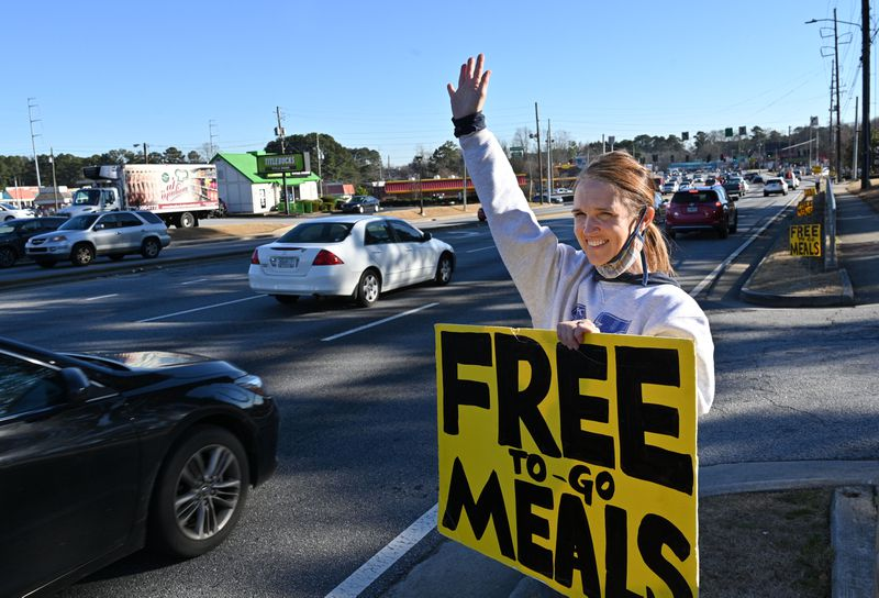 January 29, 2021 Norcross - Volunteer Janice Osborne holds up a sign on Jimmy Carter Blvd to attract attention as Chef Hank Reid and volunteers deliver ready-to-eat meals in the parking lot of The Nett Church in Norcross on Friday, January 29 .  2021. Hank Reid has been driving a food truck to bring meals where they are needed in Gwinnett County.  (Hyosub Shin / Hyosub.Shin@ajc.com)