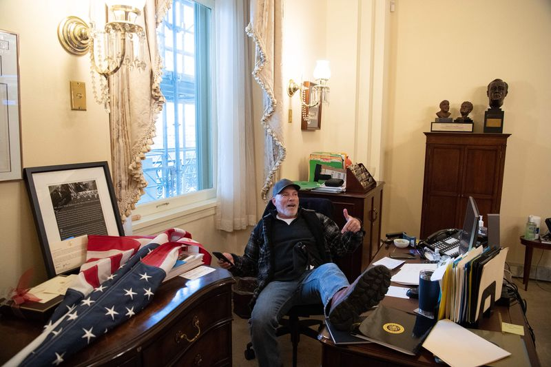 A supporter of U.S. President Donald Trump sits inside the office of U.S. Speaker of the House Nancy Pelosi as he protests inside the U.S. Capitol in Washington, D.C., on Wednesday, Jan. 6, 2021. Demonstrators breeched security and entered the Capitol as Congress debated the a 2020 presidential election Electoral Vote Certification. (Saul Loeb/AFP/Getty Images/TNS)