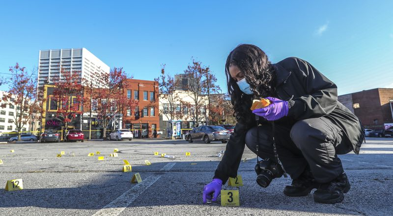 Atlanta Police Crime Technician K. Gallagher collects dozens of shell casings following a shooting outside a downtown Atlanta hookah lounge. (John Spink / John.Spink@ajc.com)