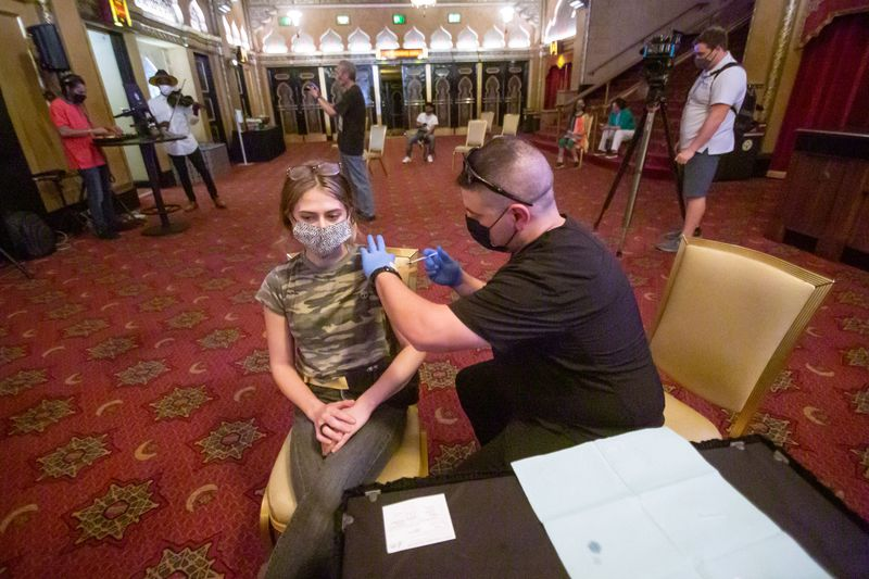 Advanced EMT Michael Williams gives Rebecca Del Plapo a COVID vaccination in the lobby of the Fox Theatre earlier this week. (Steve Schaefer for The Atlanta Journal-Constitution)