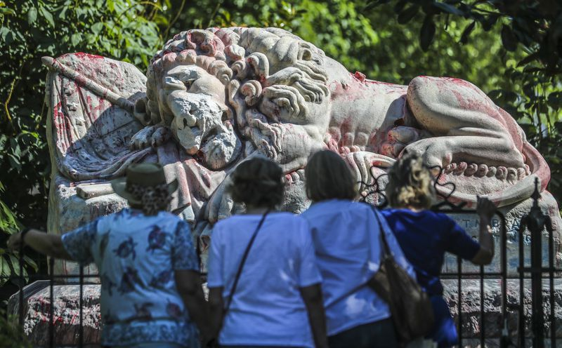 Cemetery visitors look at the results of the attempted cleaning of the statue at Oakland Cemetery in 2020. JOHN SPINK/JSPINK@AJC.COM