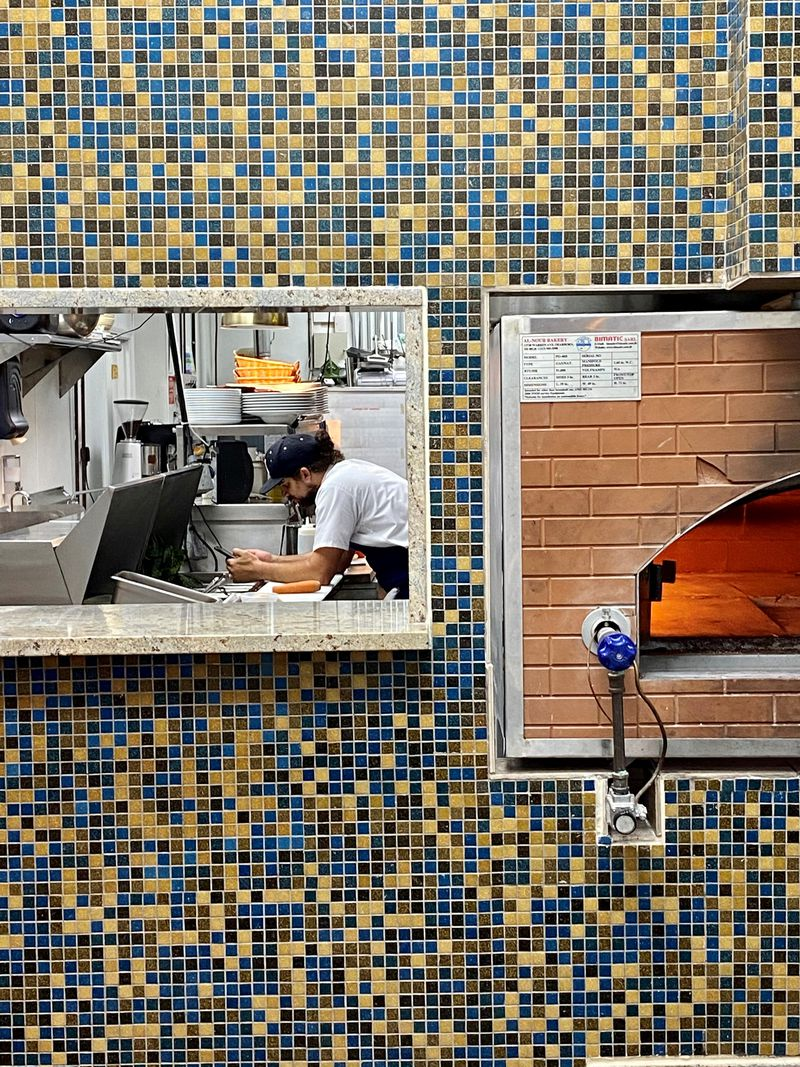 Lavie Tea, Buford Otoyolu üzerindeki Noor Kitchen'da özel bir anı yakalar.  Modern Akdeniz lokantası, sağdaki tuğla fırında kendi ekmeğini pişiriyor.  Atlanta Journal için Wendell Brook