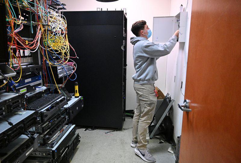 Ethan King, technician with Compass Security Solutions, checks the main alarm panel at a car dealership in Sandy Springs on Thursday, April 22, 2021. (Hyosub Shin / Hyosub.Shin@ajc.com)