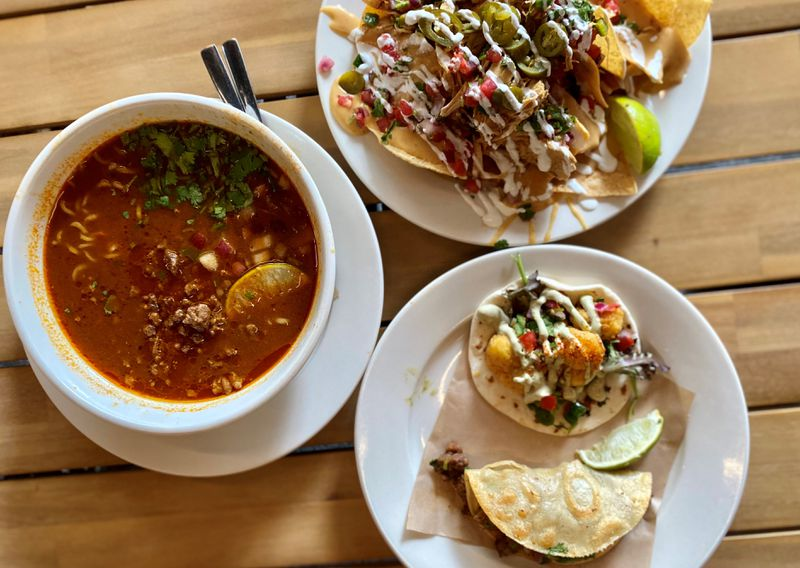 A feast from Pretty Little Tacos: (clockwise starting from the left) spicy birria ramen with steak, chicken nachos and a Creole cauliflower and steak taco. (Wendell Brock for The Atlanta Journal-Constitution)